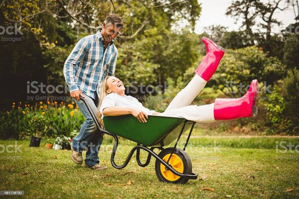 Happy couple playing with a wheelbarrow stock photo
