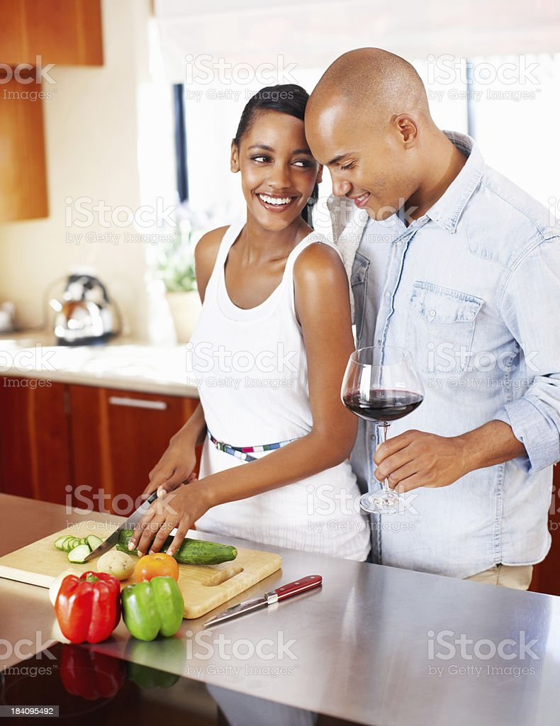 Happy couple preparing salad with man holding wine glass royalty-free stock photo