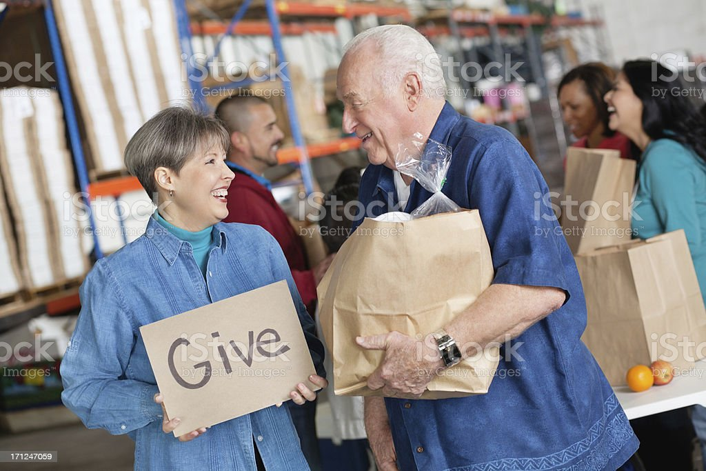 Happy couple promoting giving at an indoor donation center royalty-free stock photo