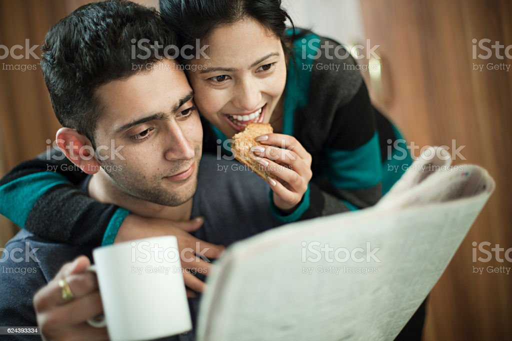 Happy couple reading newspaper, taking coffee and snacks together. stock photo