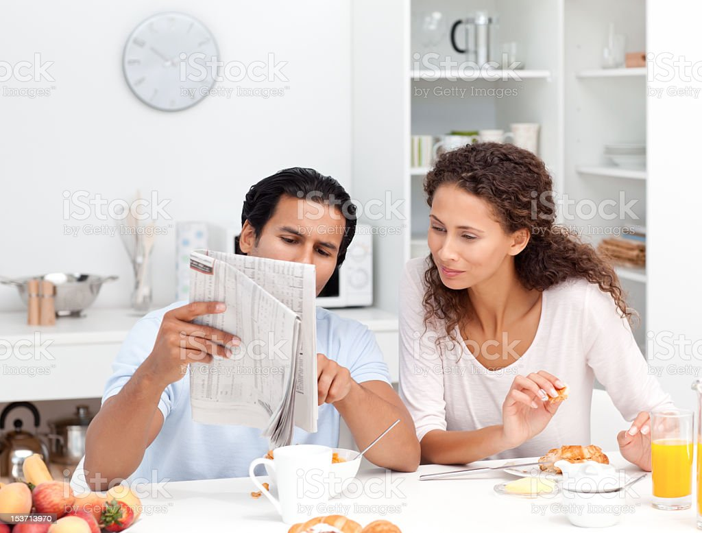 Happy couple reading the newspaper together during breakfast royalty-free stock photo