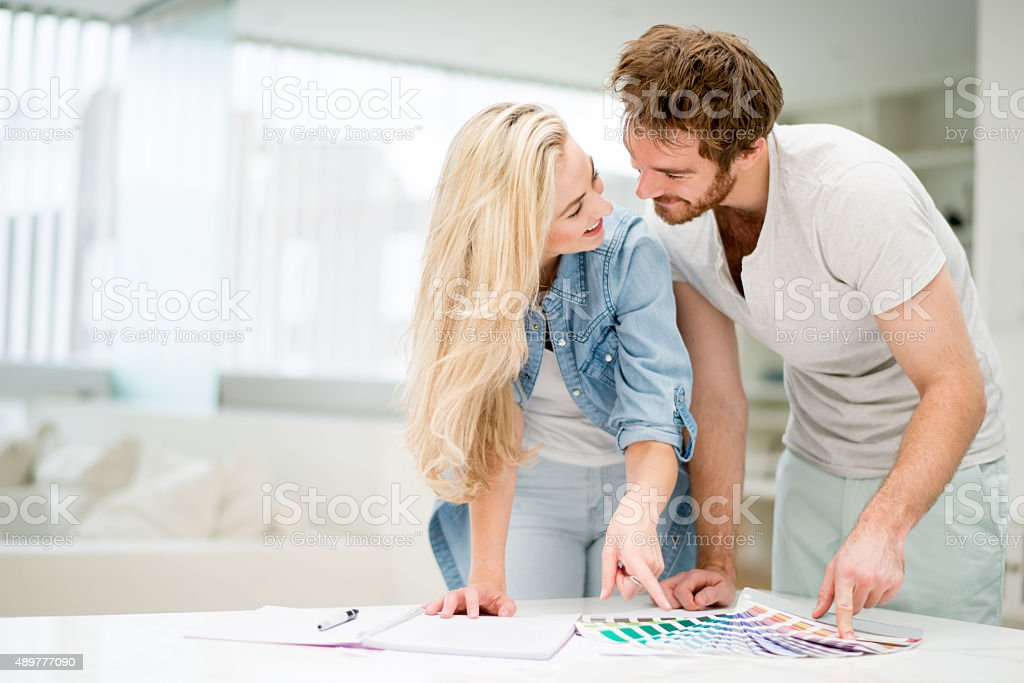 Happy couple redecorating their house stock photo