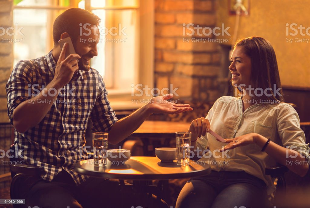 Happy couple relaxing in cafe and talking to each other. stock photo