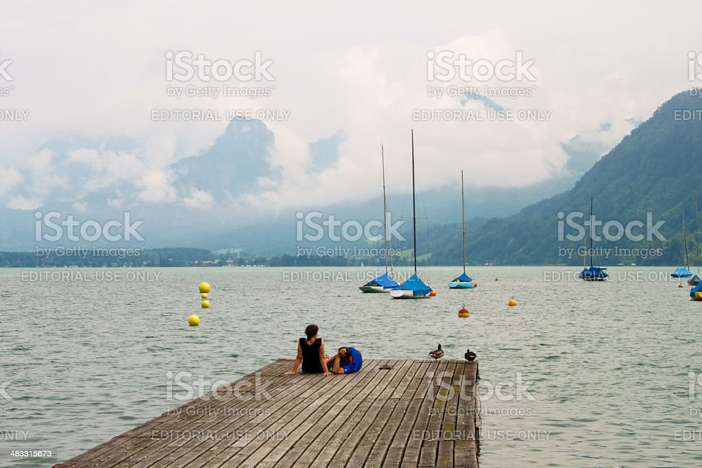 Happy couple relaxing on a pier of mountain lake stock photo