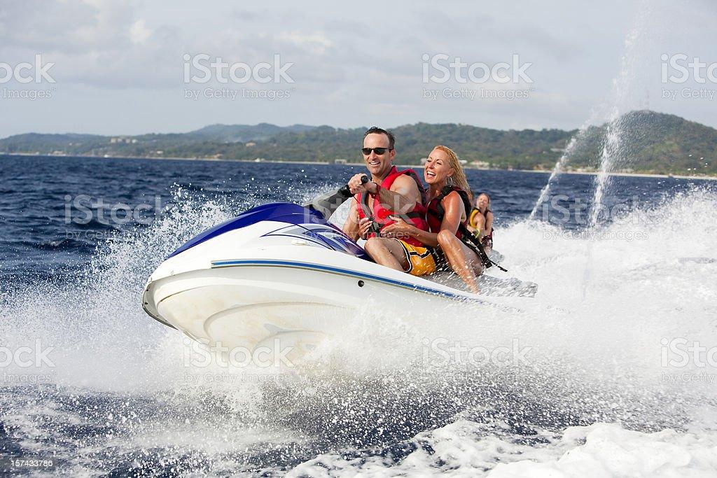 Happy couple ridding jetski stock photo