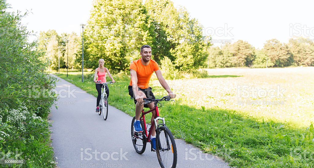 happy couple riding bicycle outdoors stock photo
