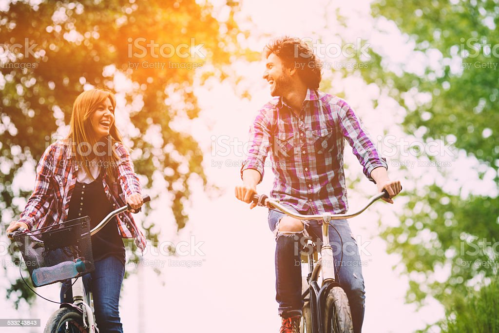 Happy Couple Riding Bicycle Together. stock photo