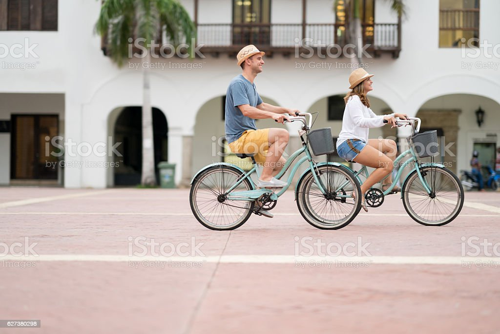 Happy couple riding bikes in the city stock photo