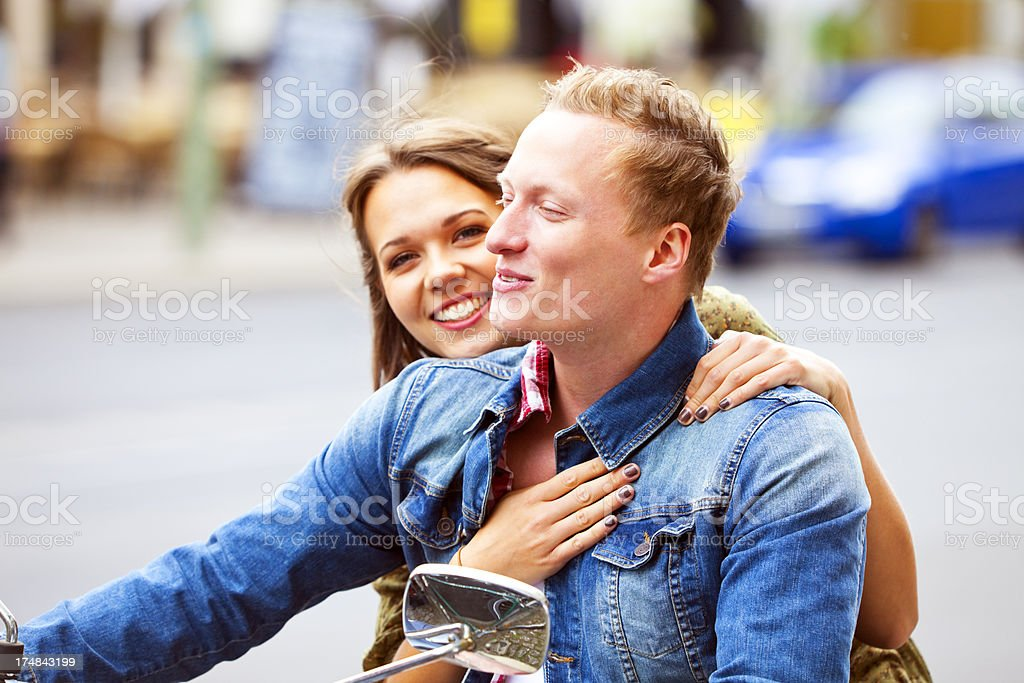 Happy Couple Riding Scooter on City Street royalty-free stock photo