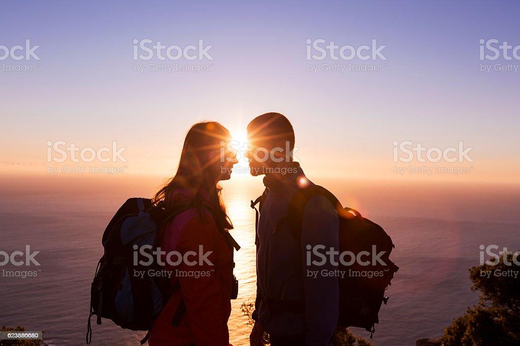 Happy couple runs through on sunlit mountain stock photo