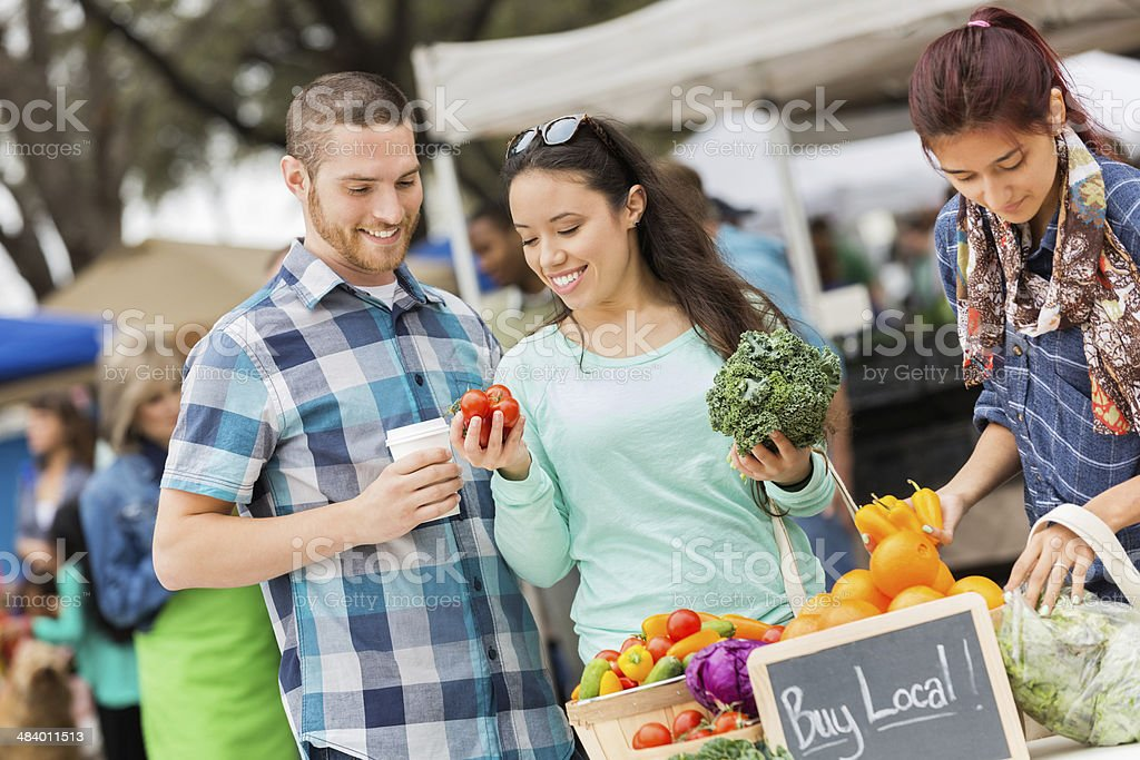 Happy couple shopping at a busy local farmers market stock photo