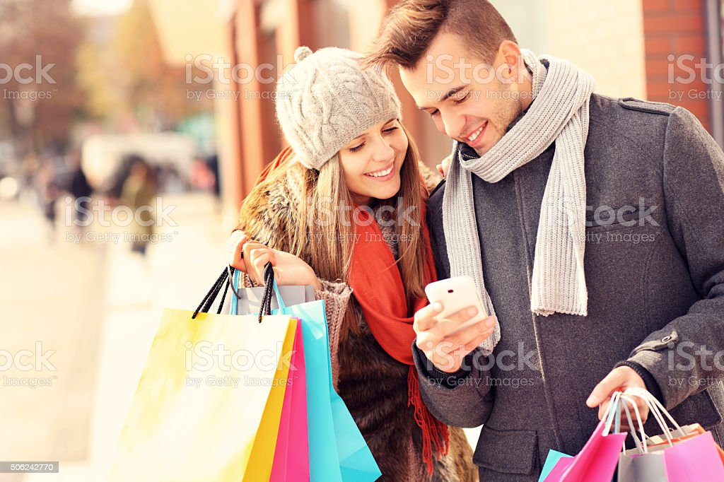 Happy couple shopping in the city with smartphone stock photo