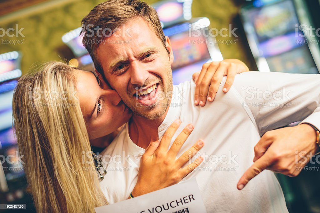 Happy Couple Showing a Gaming Voucher. Slot Machine on the...