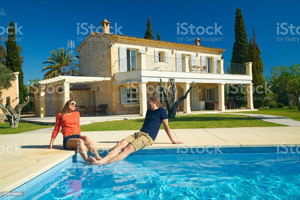 happy couple sitting at pool of rural estate stock photo