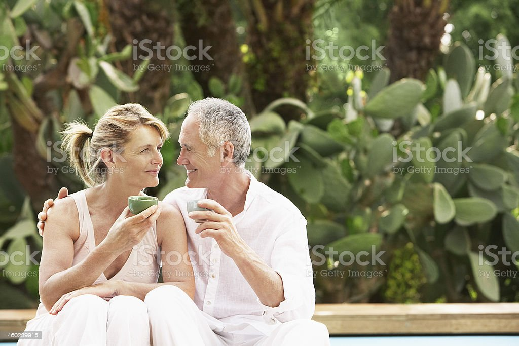 Happy Couple Sitting By Pool Drinking Tea royalty-free stock photo