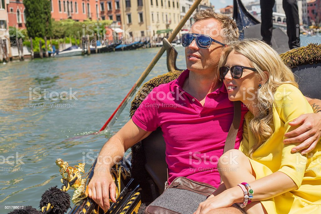 Happy couple sitting in gondola on their vacation stock photo