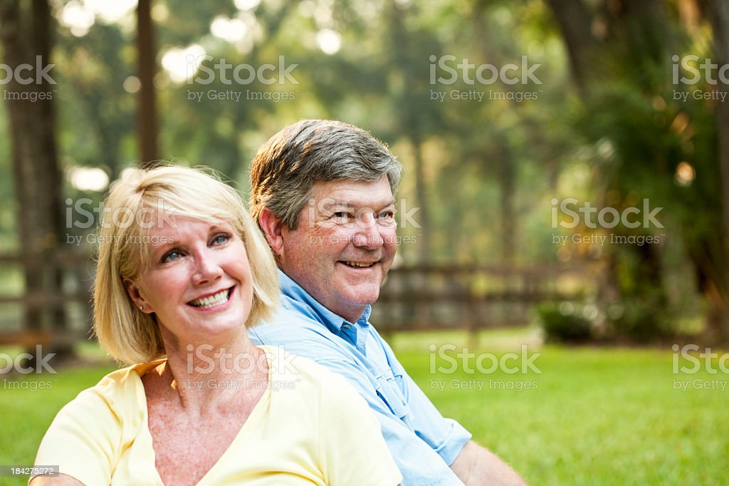 Happy couple sitting in park stock photo