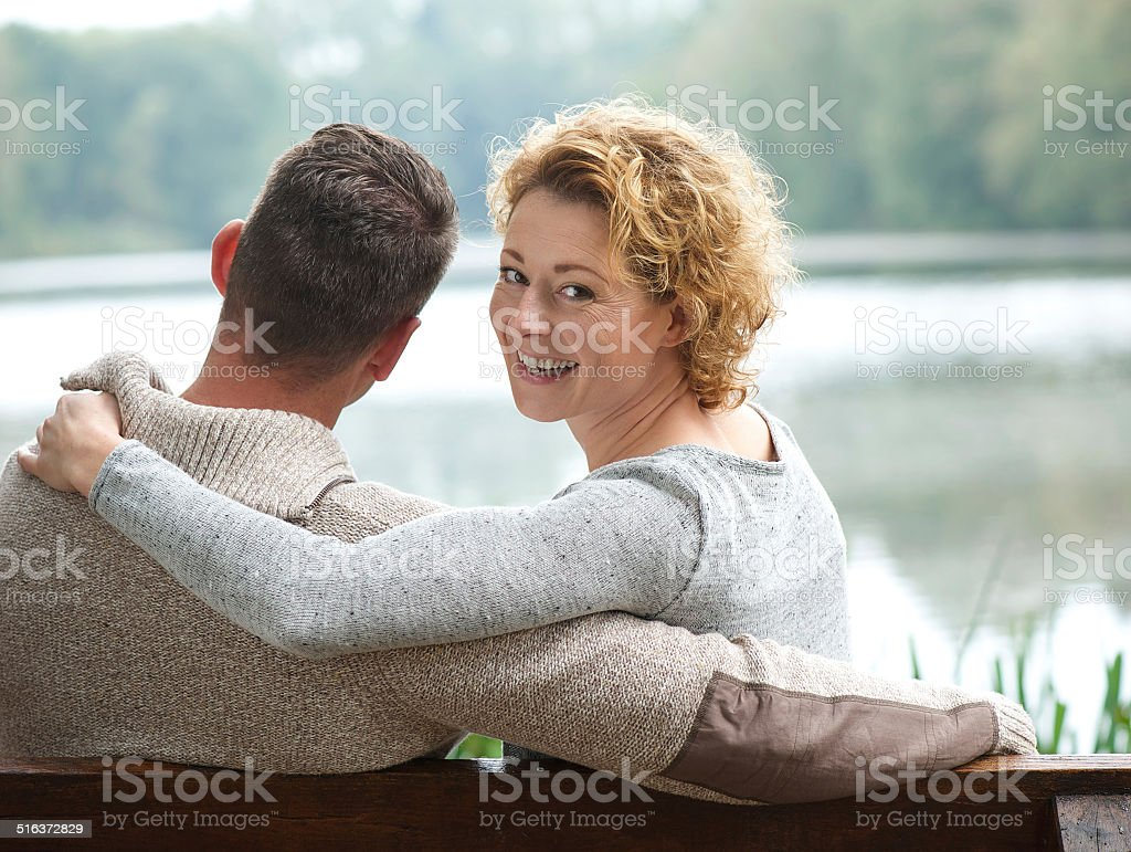 Happy couple sitting on bench outdoors stock photo