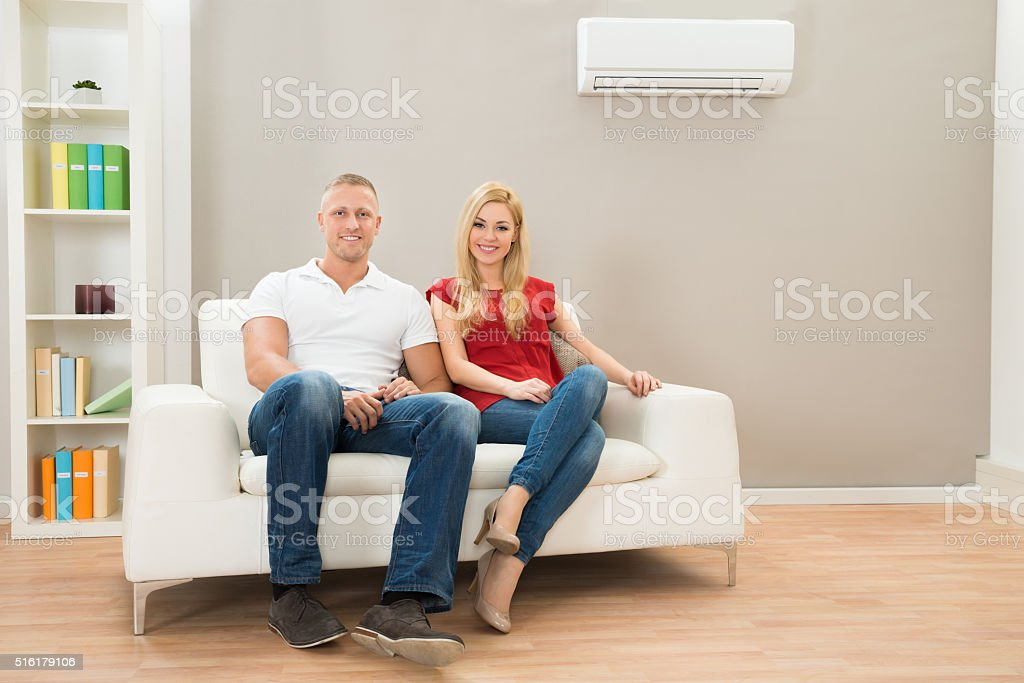 Happy Couple Sitting On Sofa stock photo