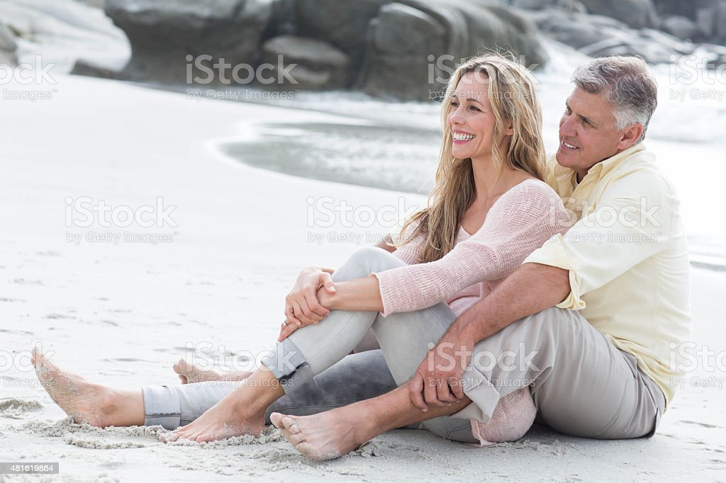 Happy couple sitting on the sand stock photo