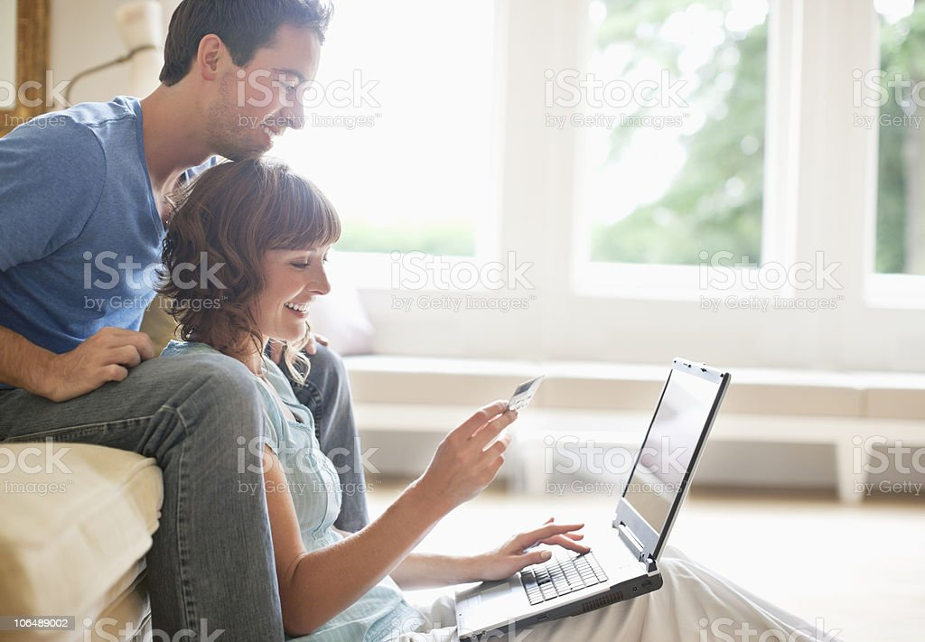 Happy couple sitting together and using laptop for online shopping stock photo