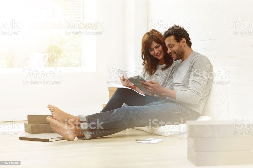 Happy couple sitting together calculating their expenses stock photo