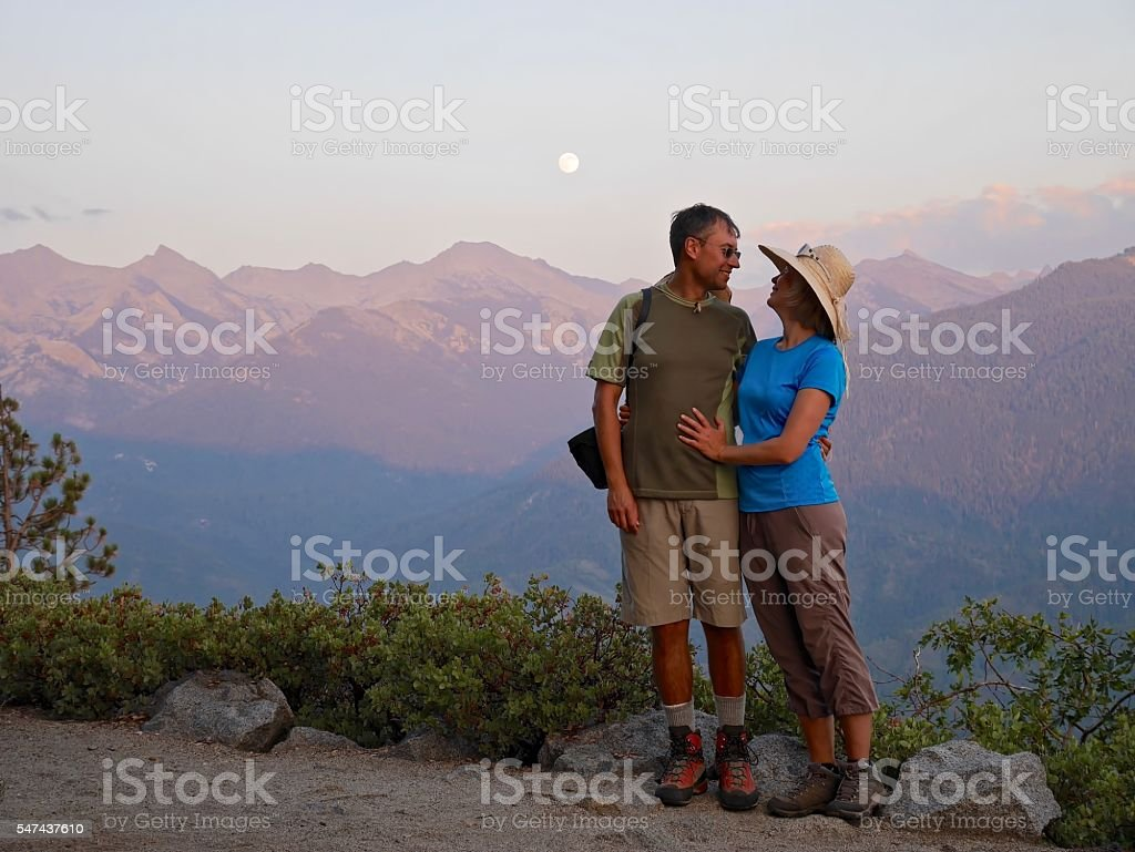 Happy couple smiling and hugging by mountains. stock photo