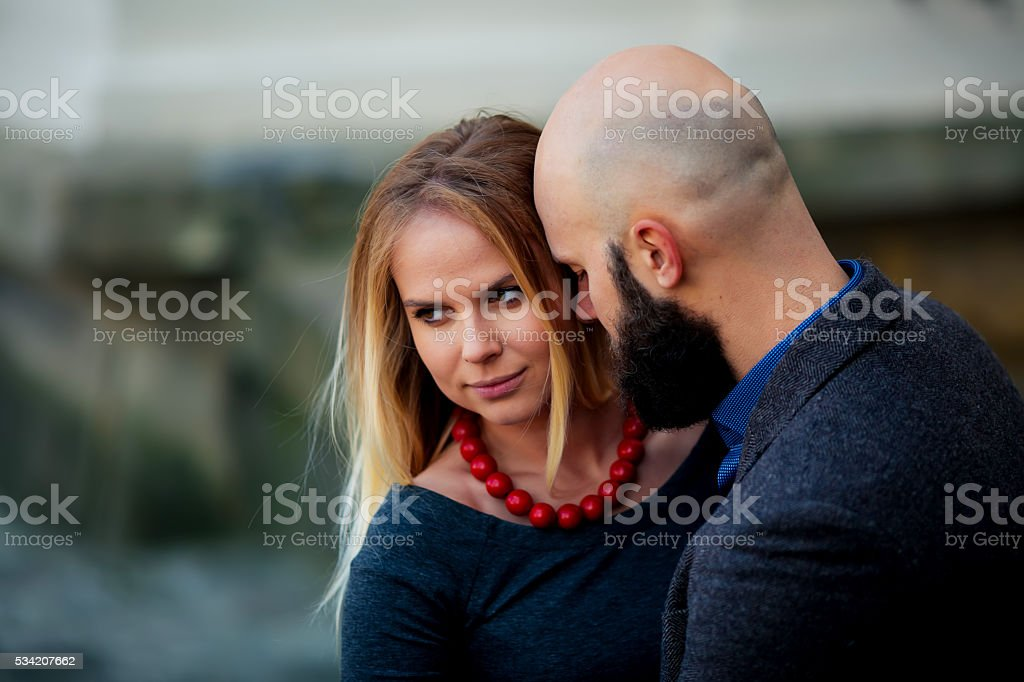 happy couple smiling, standing near the wall in the arms royalty-free stock photo