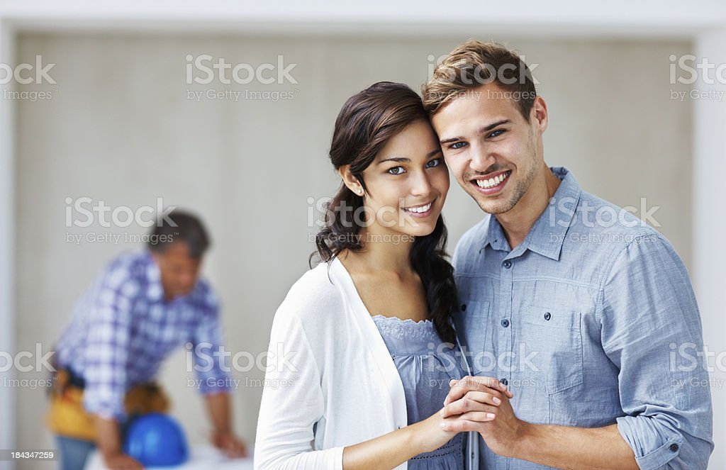 Happy couple smiling with architect in background royalty-free stock photo