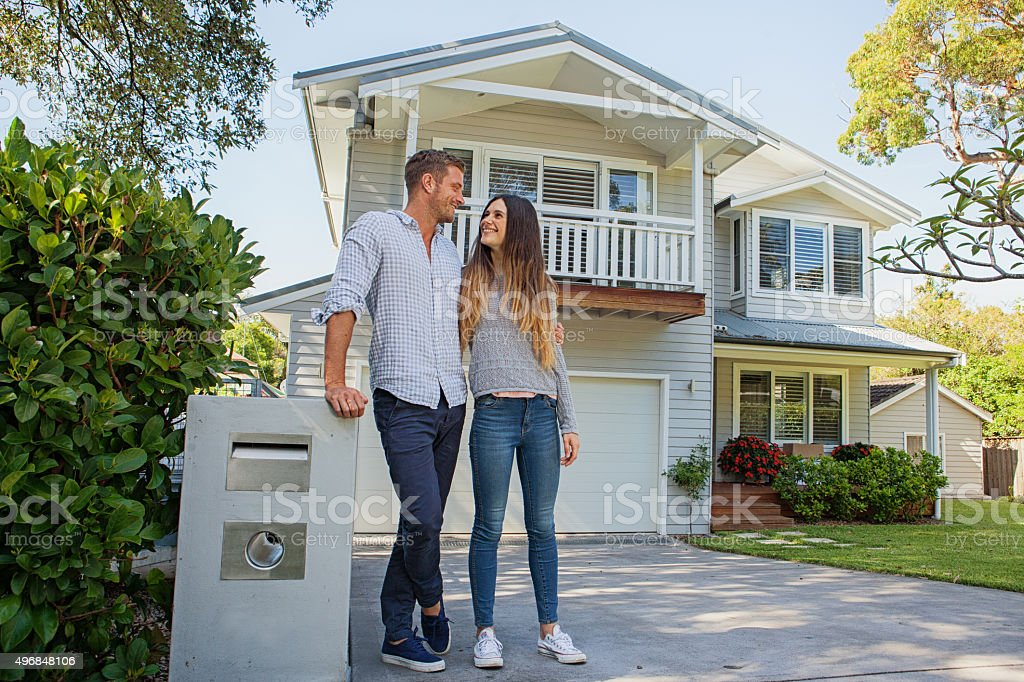 happy couple standing by mailbox in front of home stock photo