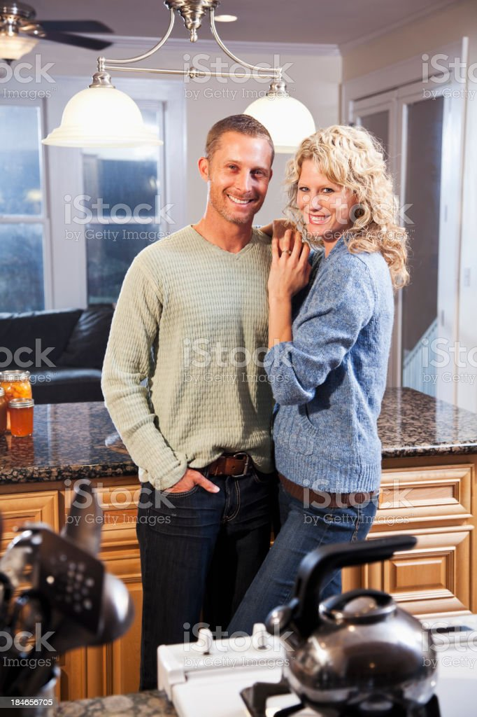 Happy couple standing in kitchen stock photo