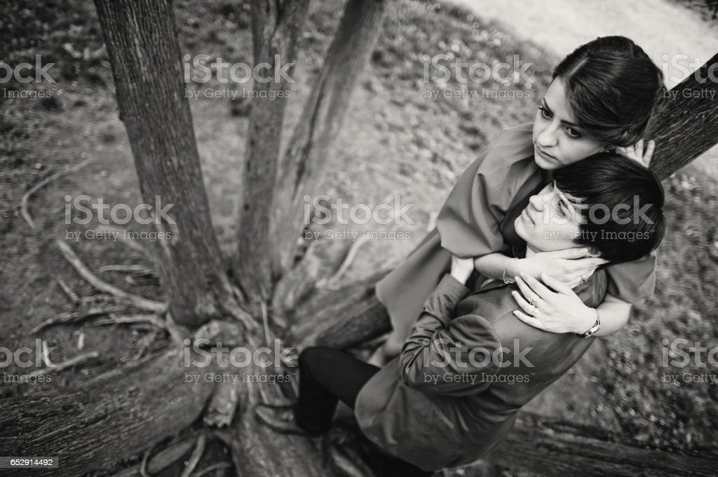 Happy couple standing on tree roots. Stylish man at velvet jacket and girl in red dress in love together stock photo