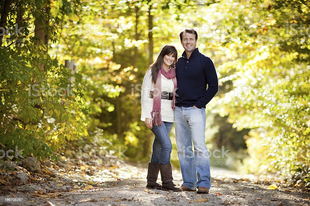 Happy Couple Standing Together in Autumn Woods royalty-free stock photo