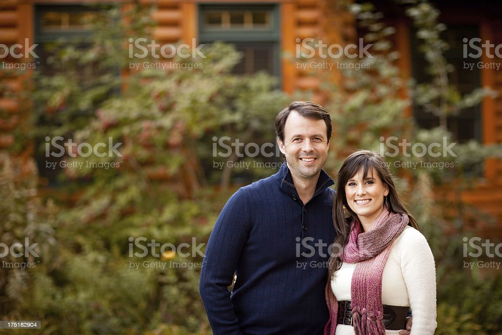 Happy Couple Standing Together Outside in Front of Log Cabin stock photo