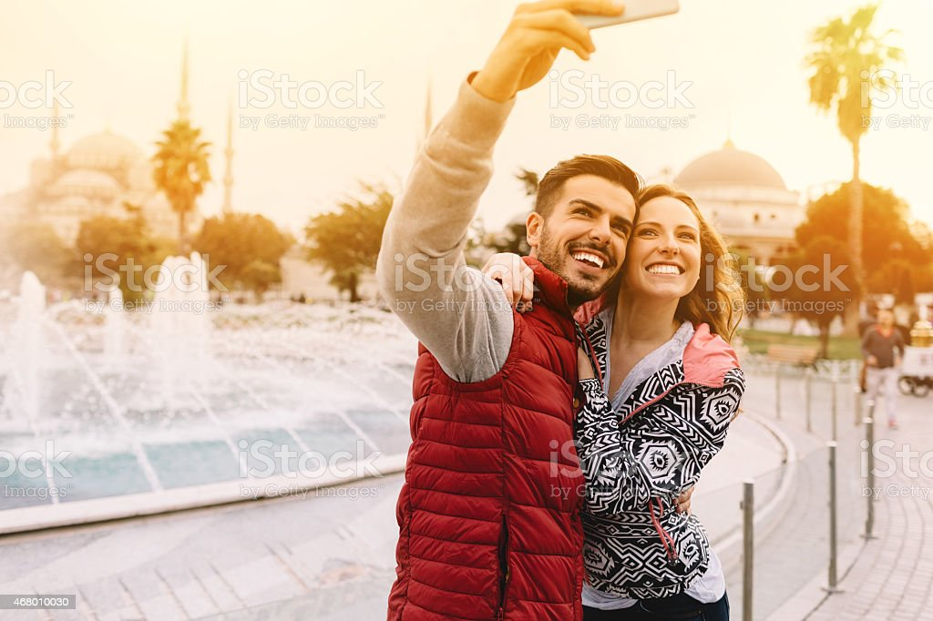 Happy couple taking a selfie in front of a fountain stock photo