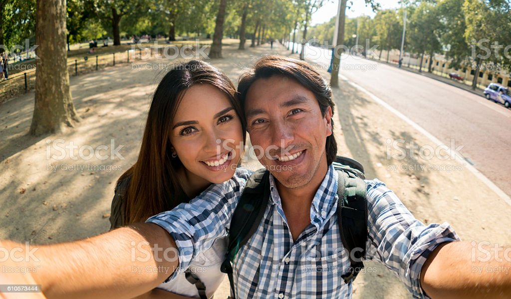 Happy couple taking a selfie outdoors stock photo