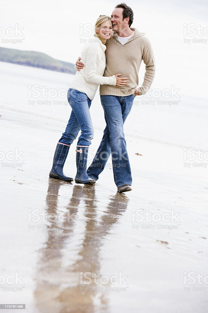 A happy couple taking a walk on the beach royalty-free stock photo
