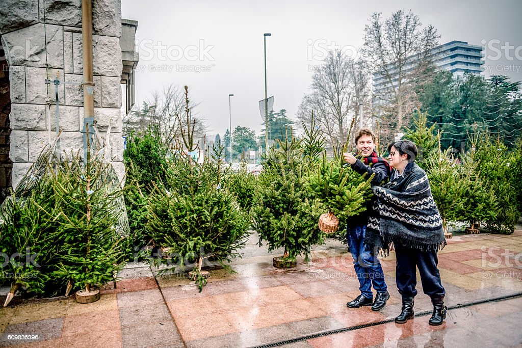 Happy Couple Taking Christmas Tree Home, City Market, Europe stock photo
