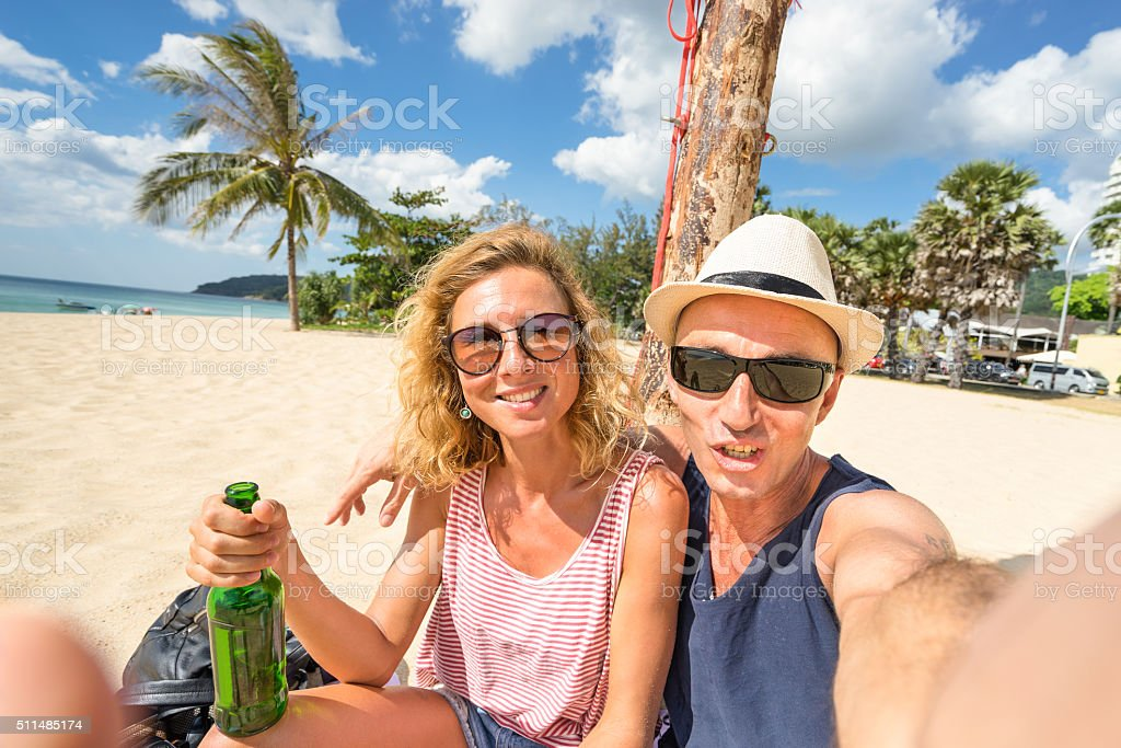 Happy couple taking selfie at beach - Travel lifestyle concept stock photo
