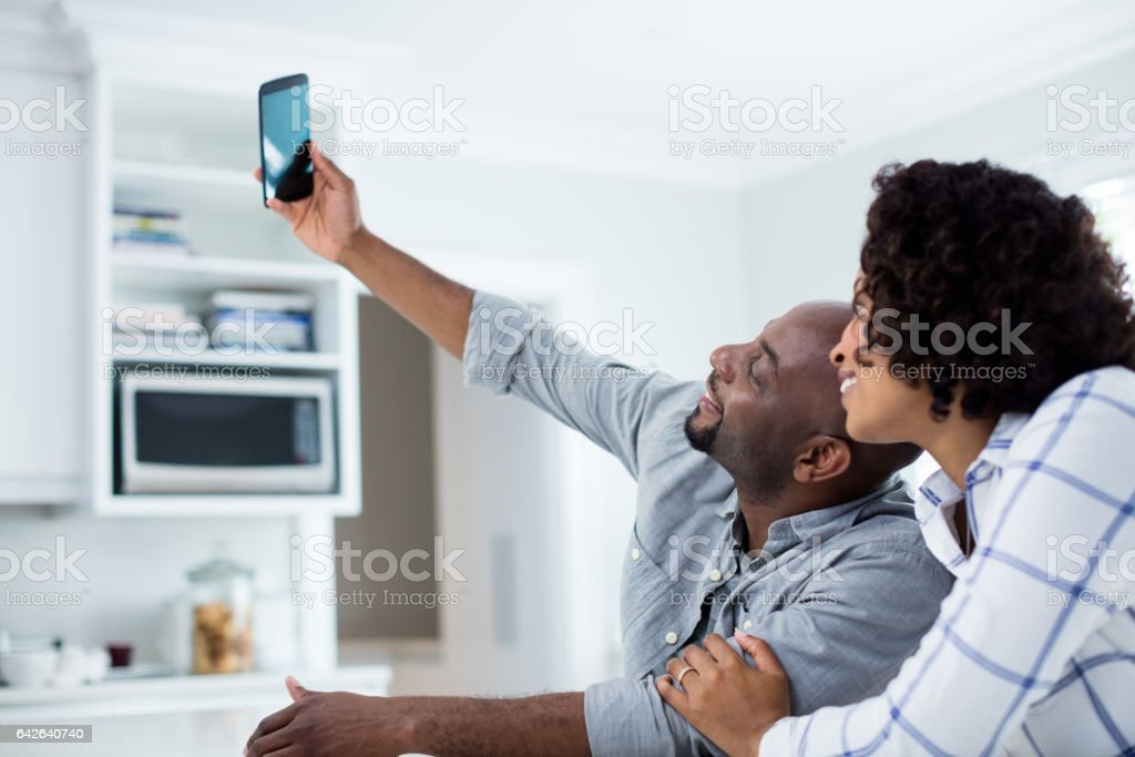 Happy couple taking selfie on mobile phone in living room stock photo