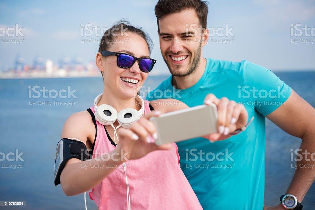 Happy couple taking selfie on the beach stock photo