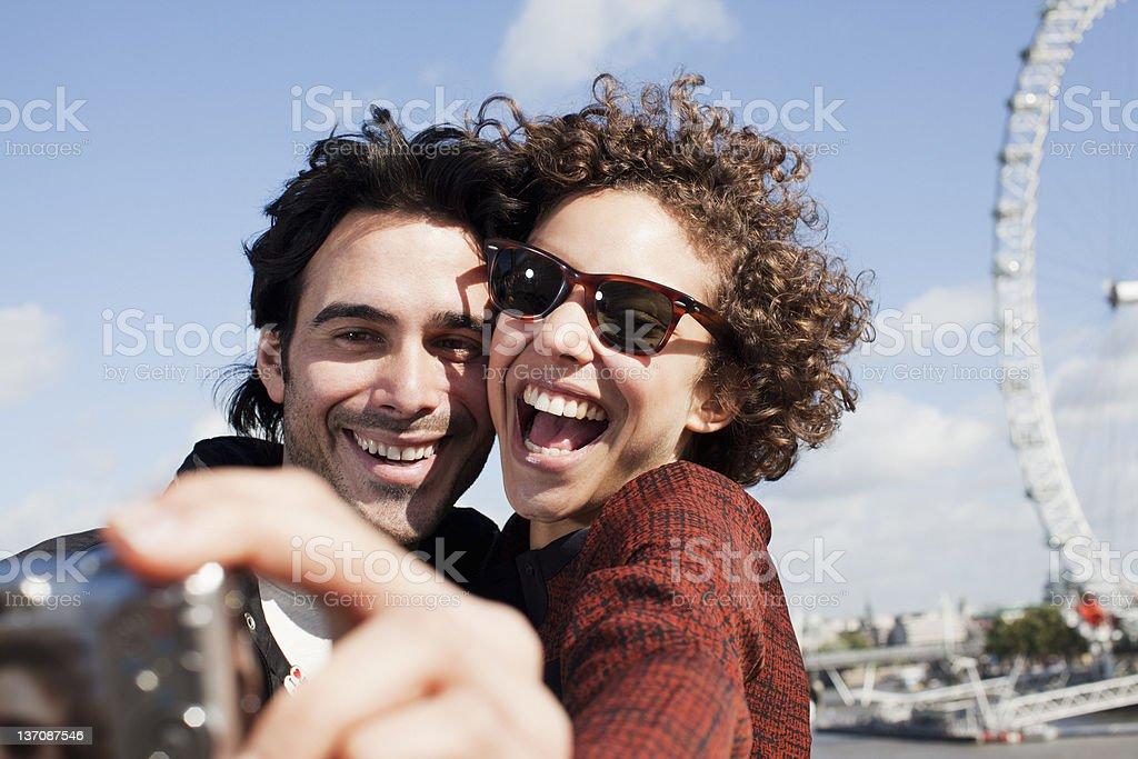 Happy couple taking self-portrait with digital camera near ferris wheel royalty-free stock photo