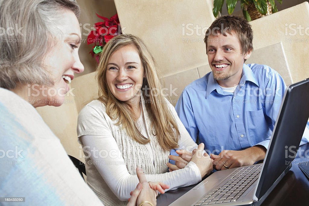 Happy Couple Talking With Advisor at Home royalty-free stock photo