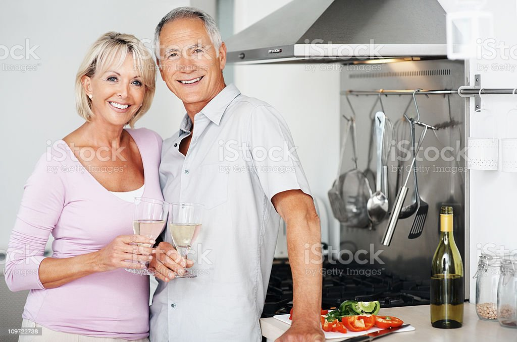 Happy couple together holding champagne glasses at kitchen stock photo