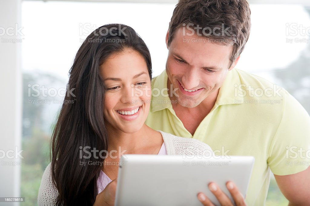 Happy couple using a digital tablet royalty-free stock photo