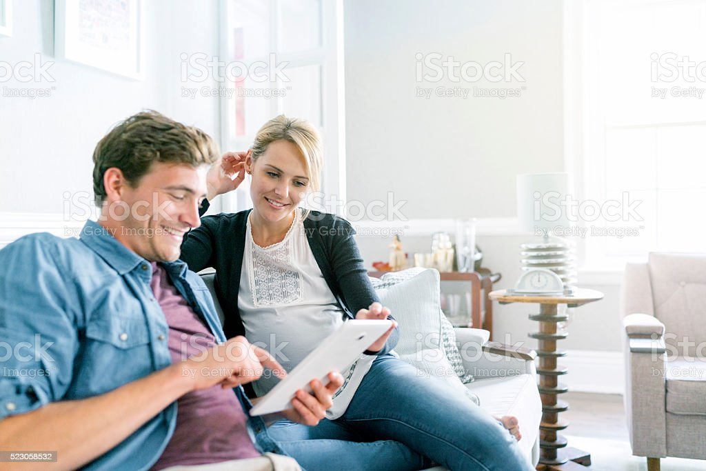 Happy couple using digital tablet on sofa stock photo