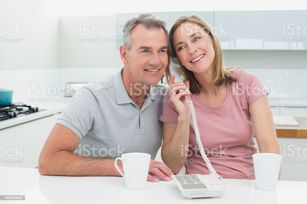 Happy couple using landline phone together in kitchen stock photo