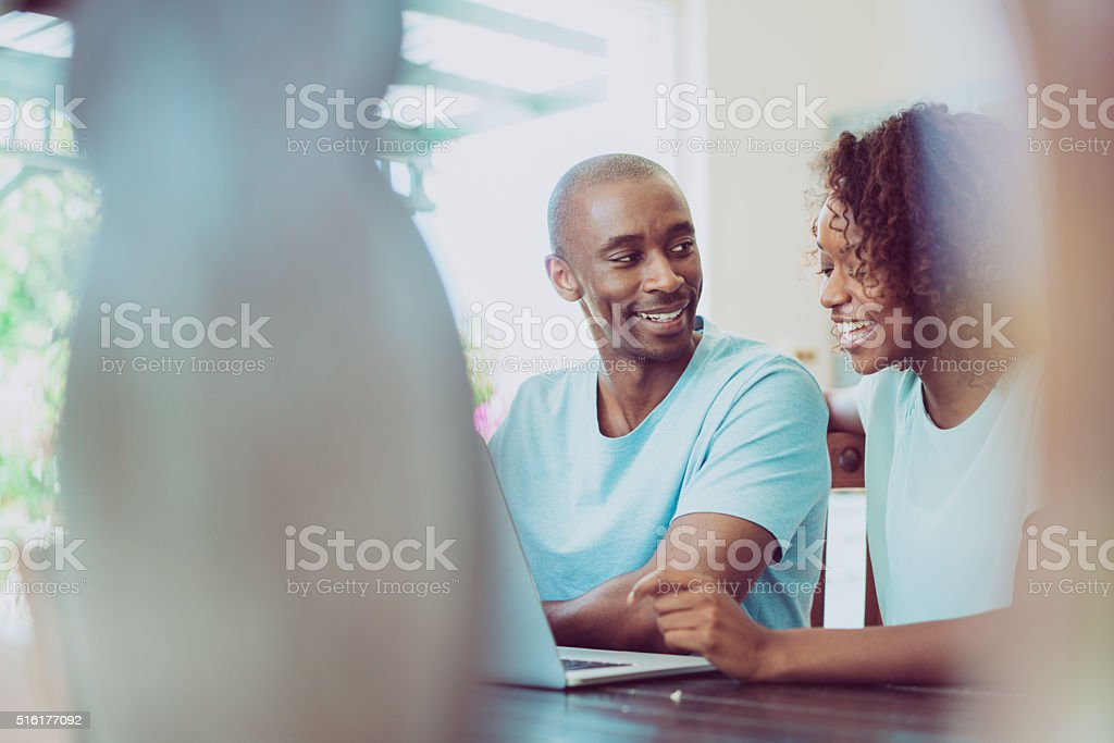Happy couple using laptop at home stock photo