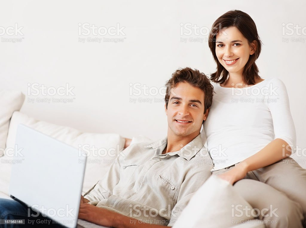 Happy couple using laptop while sitting on a couch royalty-free stock photo