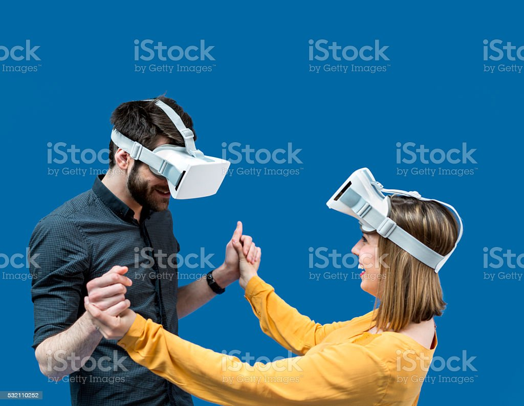 Happy couple using virtual reality glasses against blue screen stock photo